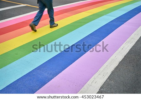 Pride Crosswalk, Vancouver. A pedestrian using the rainbow colored crosswalk in downtown Vancouver.                              - stock photo