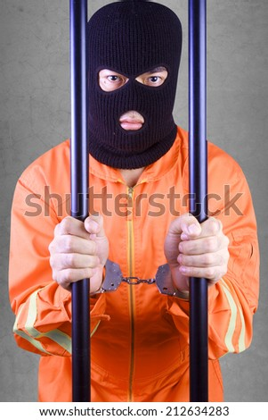 Prisoner with handcuffs wearing a balaclava camouflage face in jail of a death penalty against concrete wall  - stock photo