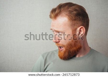 Profile of Young hipster red bearded Man standing against grey background - stock photo