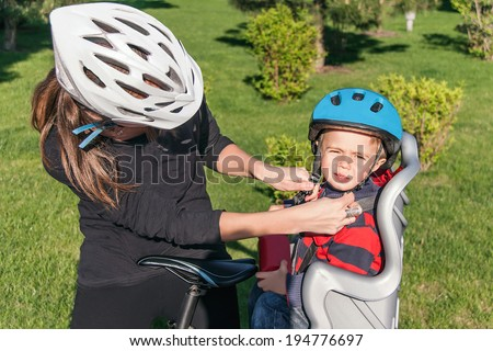 Protection on the bicycle. Caucasian mother have biking helmet and putting biking helmet on outside to her son. The son is in the bicycle chair (seat) during bicycle ride. Travel concept.  - stock photo