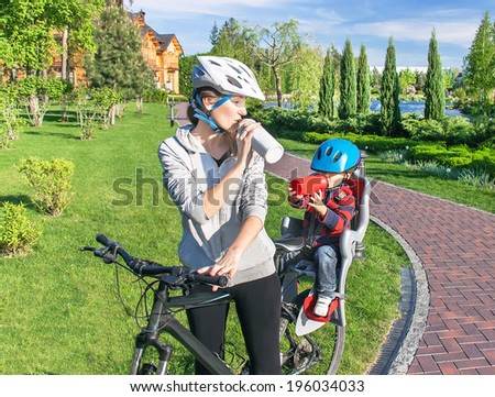 Protection on the bicycle. Caucasian woman and baby boy on a bicycle. The son is in the bicycle chair (seat). Mother and child have biking helmet on their heads and bottles of water. Travel concept.  - stock photo