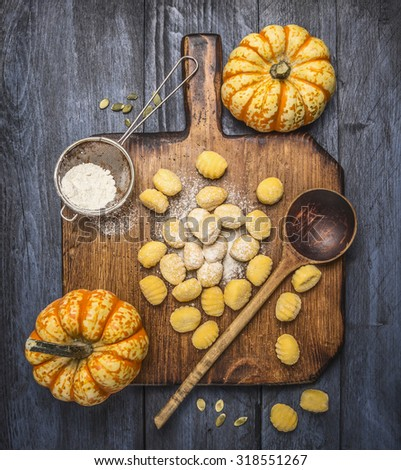 pumpkin gnocchi  with flour pumpkins spoon on a wooden cutting board on dark rustic background   top view - stock photo