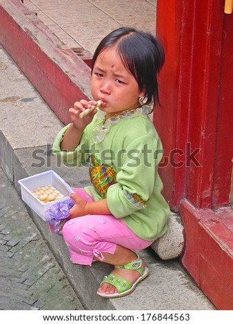 QIBAO, SHANGHAI-SEPTEMBER 4: unidentified young lady enjoying sweets. Qibao water village is Shanghai tourist attraction with 1000000 visitors year. September 4, 2004 Qibao, Shanghai.          - stock photo
