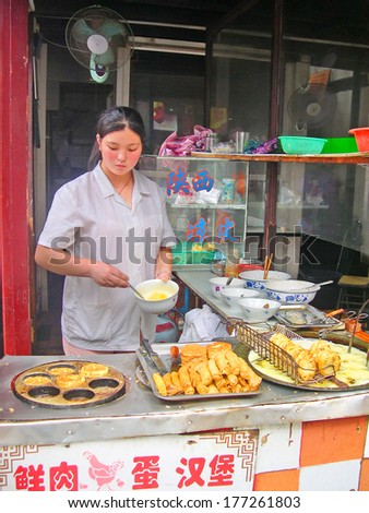 QIBAO, SHANGHAI-SEPTEMBER 4: young lady cooking and selling snacks. Qibao water village is Shanghai tourist attraction with 1000000 visitors year. September 4, 2004 Qibao, Shanghai.          - stock photo
