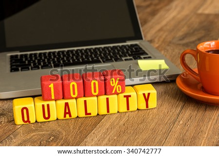 100% Quality written on a wooden cube in a office desk - stock photo