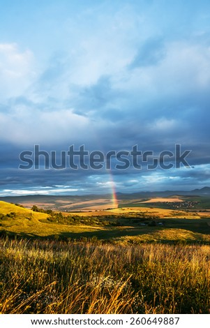 Rainbow and Massive Clouds at Sunrise in a Valley - stock photo