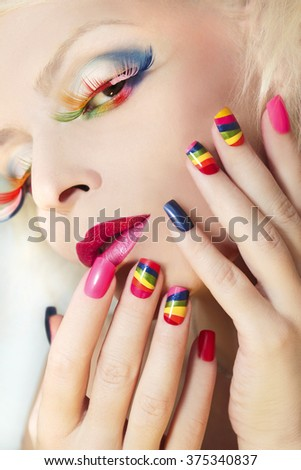 Rainbow manicure on artificial nails square shape on the girl and colorful makeup.  - stock photo