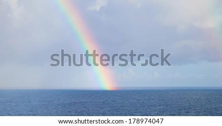 Rainbow over sea - stock photo