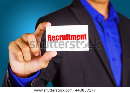 """Recruitment"" black and red text on white card hold by young business man wearing a business jacket - economic, finance and crisis concept - stock photo"