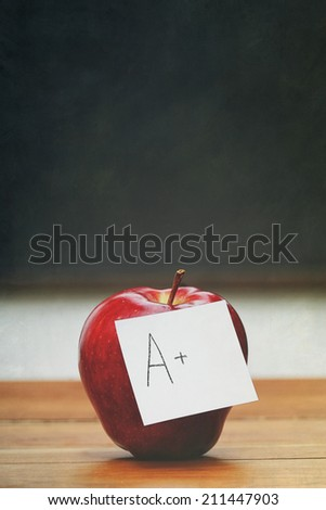 Red apple with note on desk with blackboard in background - stock photo