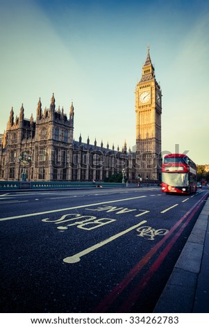 Red bus in motion and Big Ben, the Palace of Westminster in London, Uk. - stock photo