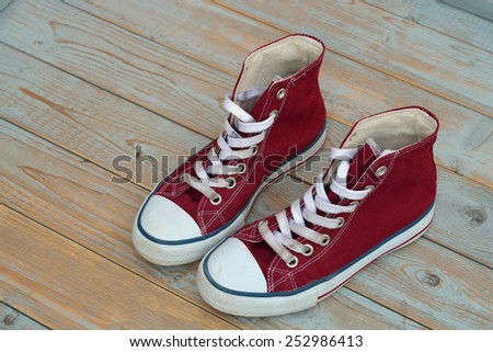 red canvas sneakers on a old wooden background - stock photo