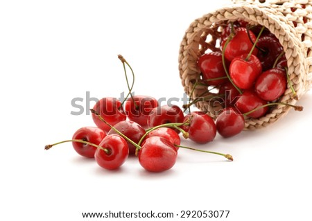Red cherries spilling out from the basket on white background - stock photo