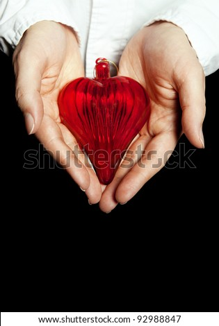 Red heart in hand isolated on black background.Health insurance concept. - stock photo
