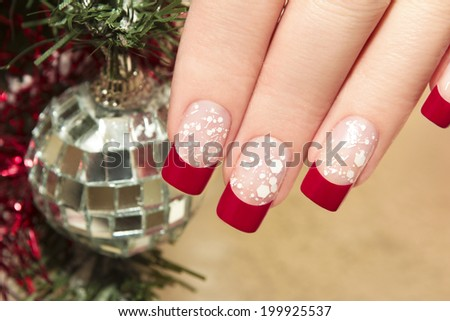 Red nail Polish on artificial nails with white crumb and new year's accessories. - stock photo