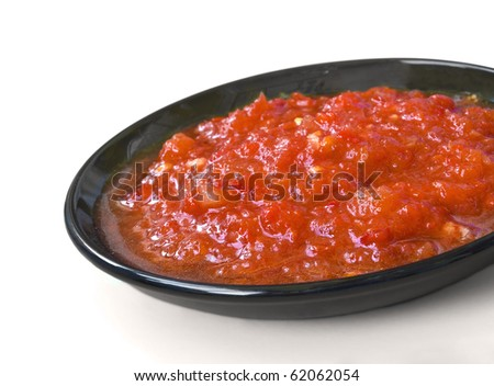 Red sauce on the black saucer isolated over white background - stock photo