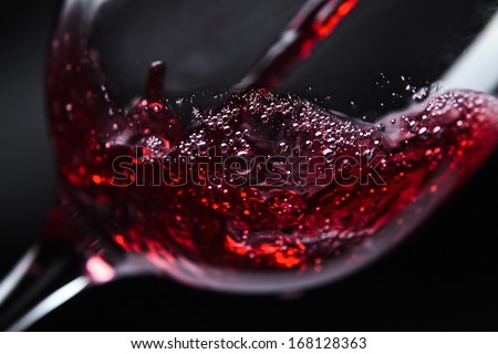 Red wine in wineglass on  black background - stock photo