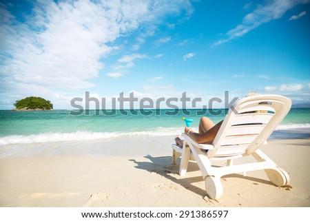 Relaxing and enjoying on summer vacation, woman with cocktail lying in sunbed on beach  - stock photo