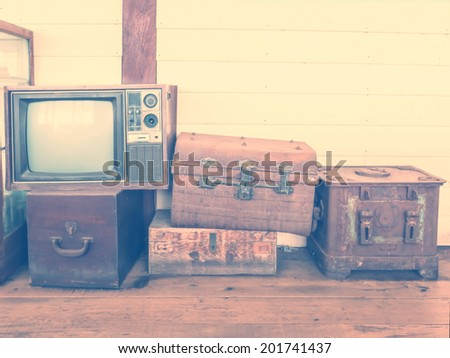 retro tv and boxes on wooden floor with vintage filter effect - stock photo