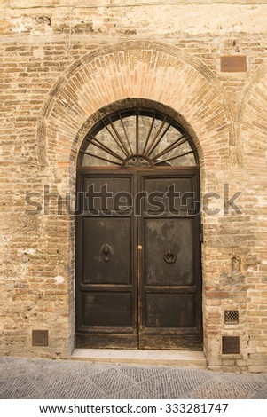 Retro wooden door outside old Italian house in a small town of San Germignano, Tuscany Italy.  ivy, vintage - stock photo
