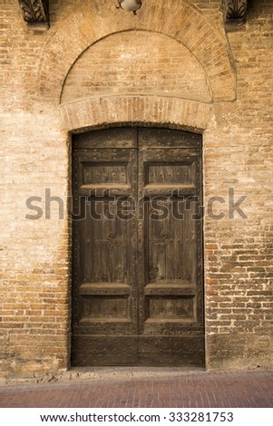 Retro wooden door outside old Italian house in a small town of San Germignano, Tuscany Italy., ivy, vintage - stock photo