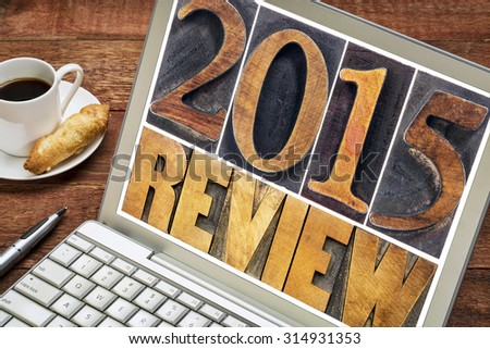 2015 review - annual review or summary of the recent year - text in letterpress wood type blocks on a laptop screen with a cup of coffee - stock photo