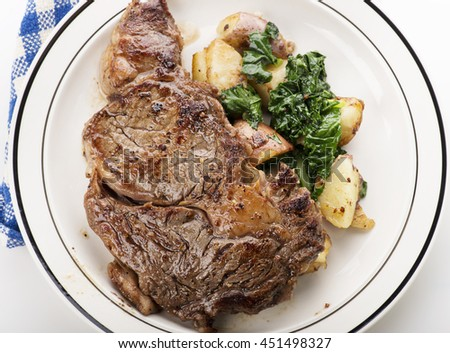 Rib Eye steak with potatoes and spinach - stock photo