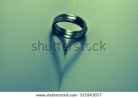 Ring and heart shaped shadow over a Bible - stock photo