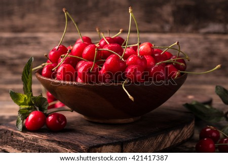 Ripe Cherries on wooden table with water drops  - stock photo