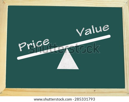 rising value and decreasing price on a scale, with chalkboard background - stock photo