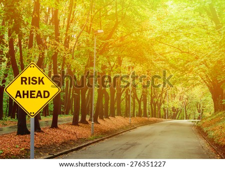 """RISK AHEAD"" sign against road in green forest - Business concept - stock photo"