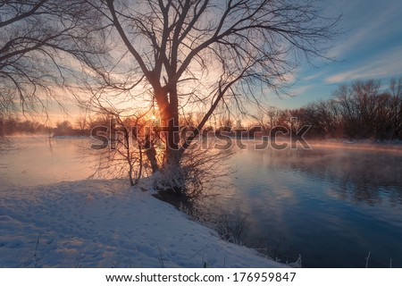 Riverbank in winter snowy sunrise landscape. - stock photo