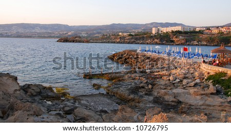 Rocky beach with people relaxing on a beach Pavilion. - stock photo