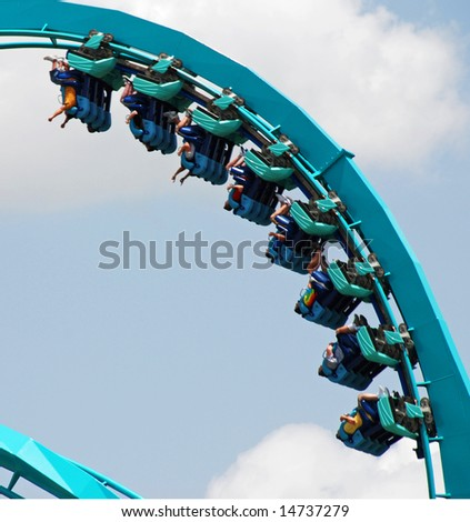 Roller Coaster with people taking a ride. - stock photo