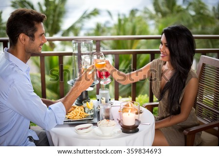 Romantic couple on the balcony toasting during dinner - stock photo