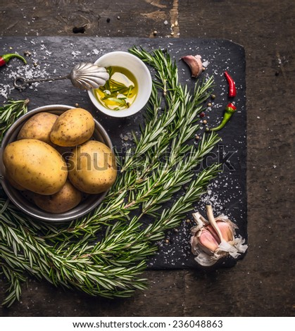 rosemary Potatoes preparation with oil,garlic and spices on dark slate and wooden background - stock photo