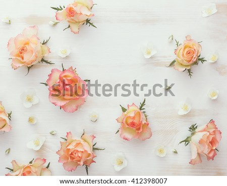 Roses and jasmine natural flower background. Various soft roses and and jasmine flowers scattered on a vintage background, overhead view, vintage toned image - stock photo