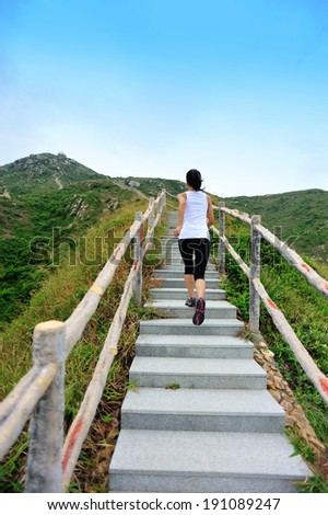 Runner athlete running at mountain stone stairs. woman fitness jogging  workout wellness concept.   - stock photo