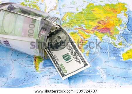 17.08.2015 - Russia - Moscow - studio, glass jar with dollars on the world map - stock photo