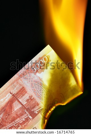 5000 russian rubles bill on fire over black background - stock photo