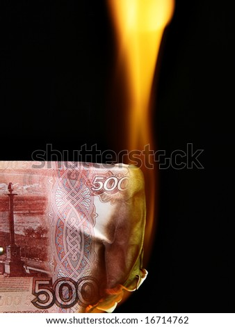 5000 russian rubles bills on fire over black background - stock photo