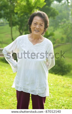 80's Asian senior woman back pain after exercise in the park at morning - stock photo