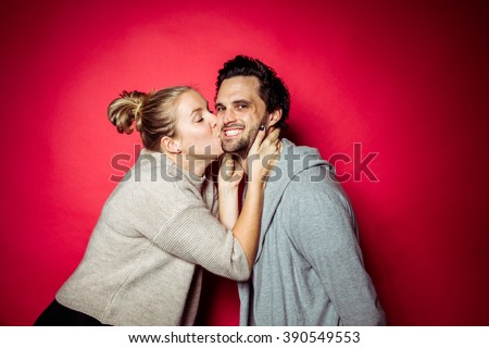 20s Couple in Photostudio in front of beige backdrop having fun in front of the camera with spot light with contrasty vibrant look kissing each other - stock photo