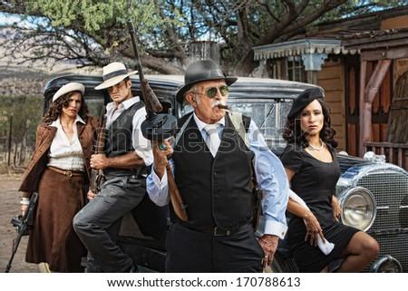 1920s dangerous criminals with guns next to vintage car - stock photo