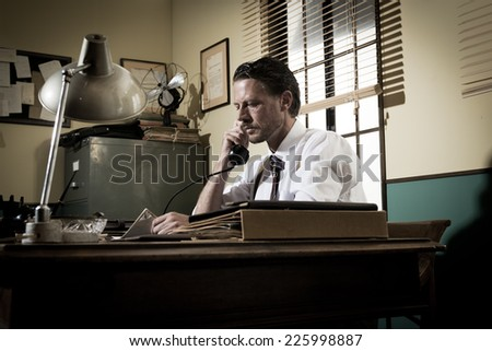1950s office: confident director on the phone working at desk. - stock photo