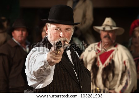 1800s style man in old west theme points his gun - stock photo