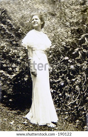 1930's vintage black and white soft focus. Young woman walking in long white gown. - stock photo