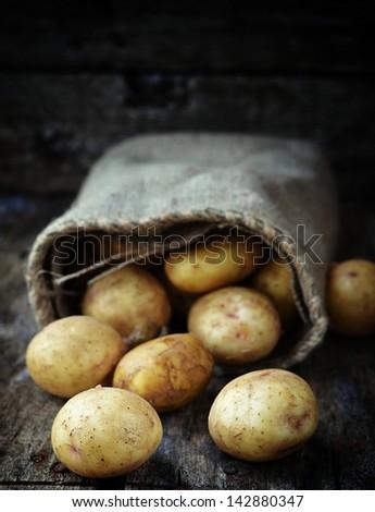 Sack fresh organic potatoes on a wooden table - stock photo