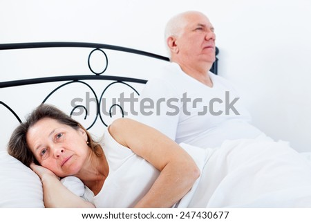 Sad mature woman  turned away from   elderly man sitting on   bed - stock photo