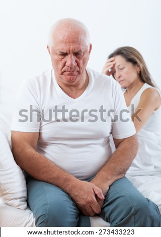 Sad senior man  turned away from   mature woman sitting on   bed - stock photo